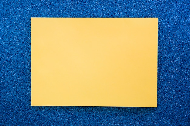 Elevated view of yellow cardboard paper on blue backdrop