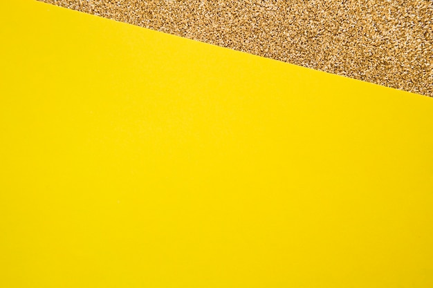 Elevated view of yellow cardboard paper on golden carpet