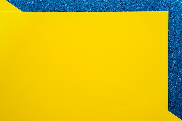 Elevated view of yellow cardboard papers on blue surface