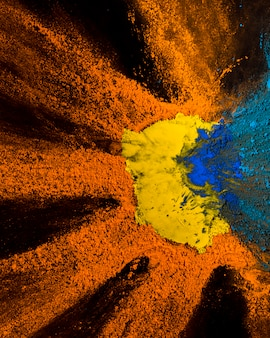 Elevated view of yellow,orange and blue holi powder design on black backdrop