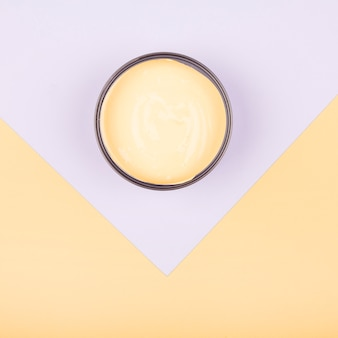 An elevated view of yellow paint container on dual paper background