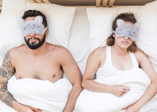 Elevated view of young couple lying on bed with an eye mask