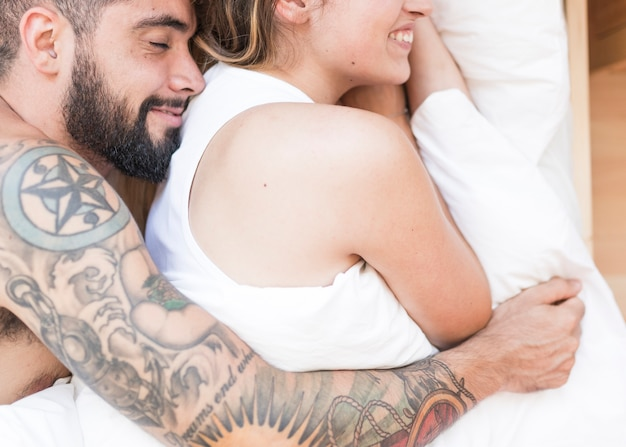 Elevated view of young couple sleeping together on bed