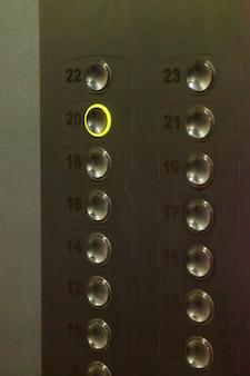 20번이 활성화된 엘리베이터 버튼. 키보드 또는 엘리베이터 제어판. 아파트 건물의 엘리베이터 내부입니다. 레코딩 버튼 20입니다. 2020년의 개념