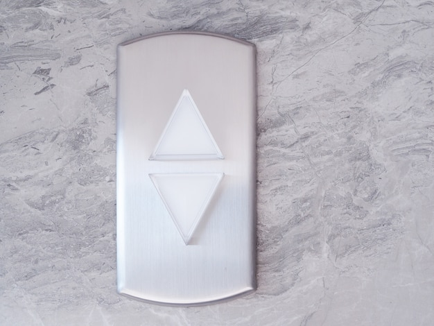 Elevator with lift silver button triangle up and down on marble pattern wall.
