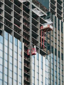建設中の超高層ビルの建設現場にエレベーターが上がる