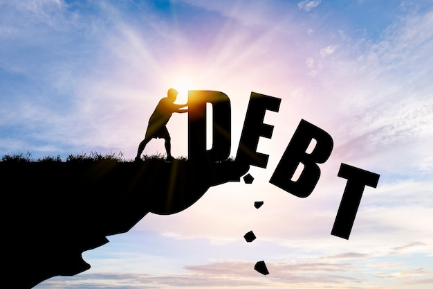 Eliminate or get rid of debt concept , silhouette man pushed off debt wording a cliff with blue cloud sky and sunlight.