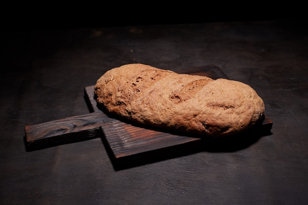 Eliptic form bread on a black, bread from a stove on dark boards