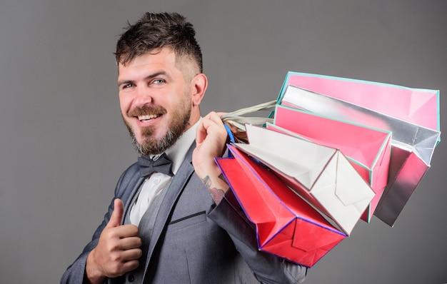 エリートブティック。男ひげを生やしたエレガントなビジネスマンは灰色の背景に買い物袋を運びます。ショッピングをもっと楽しくしましょう。ブラックフライデーのお得なショッピングをお楽しみください。ディスカウント付きのショッピングは購入をお楽しみください。