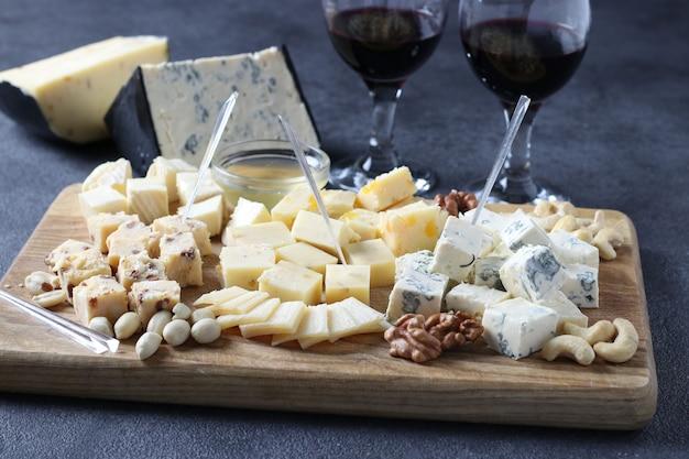 Элитные сыры: с трюфелем, дор-блю, бри, пармезаном и ассорти из орехов на деревянной доске. закуска на винную вечеринку
