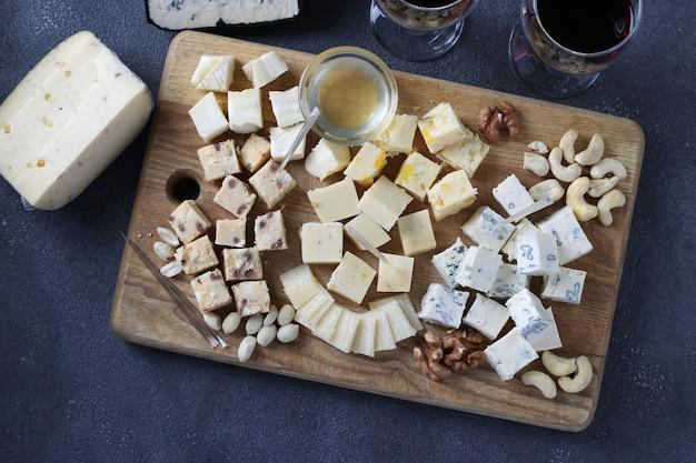 엘리트 치즈: 회색 배경에 나무 판자에 트러플, 도르 블루, 브리, 파르메산, 견과류 모듬. 와인 파티 간식. 위에서 보기