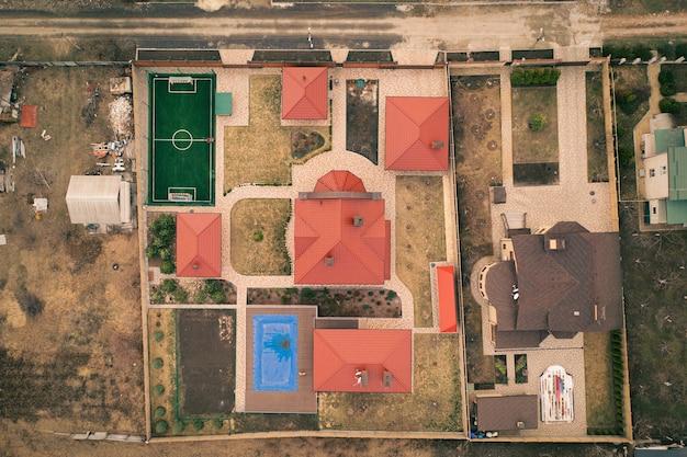 Элитный загородный коттедж во дворе с домиками и газонами с высоты птичьего полета роскошная вилла с черепичной крышей во дворе с бассейном и футбольным полем