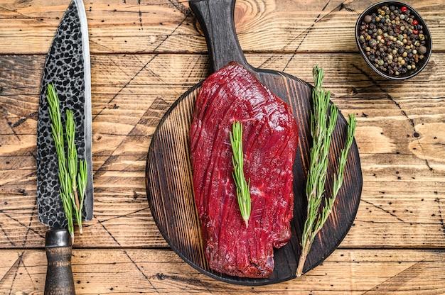Сырой стейк из дикого мяса лося на разделочной доске. деревянный стол. вид сверху.