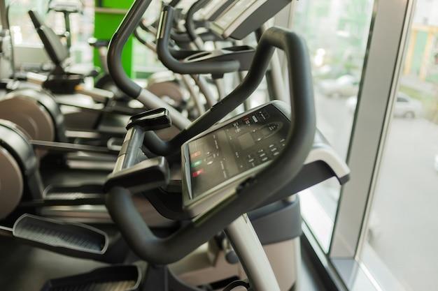 Эллиптические тренажеры в тренажерном зале. фитнес, концепция здорового образа жизни.