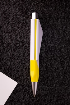 Ellow pen and white card on dark background.