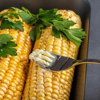 Elote corn은 베이킹 시트에 치즈 또는 파마산 치즈, 고수, 향신료 및 칠리를 뿌립니다.