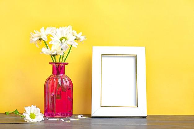 ピンクのスタイリッシュな花瓶で柔らかいアスターの花とフレームのモックアップ。ポスターの白いフレームモックアップ。 em