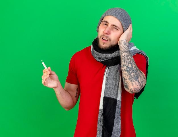 겨울 모자와 스카프를 착용 한 젊은 백인 아픈 남자가 머리에 손을 댄다.