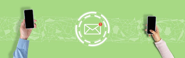 Email concept. hands with a smartphone on a green background with graphics.