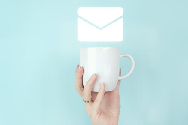 이메일 마케팅 개념입니다. 여자 손은 파란색 배경에 기호 이메일 아이콘이 있는 모닝 커피 컵을 잡고 있습니다. 문의 개념입니다.
