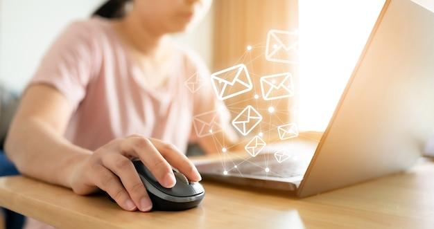 이메일 마케팅 개념입니다. 봉투 아이콘이 있는 컴퓨터를 사용하여 메시지를 보내는 손