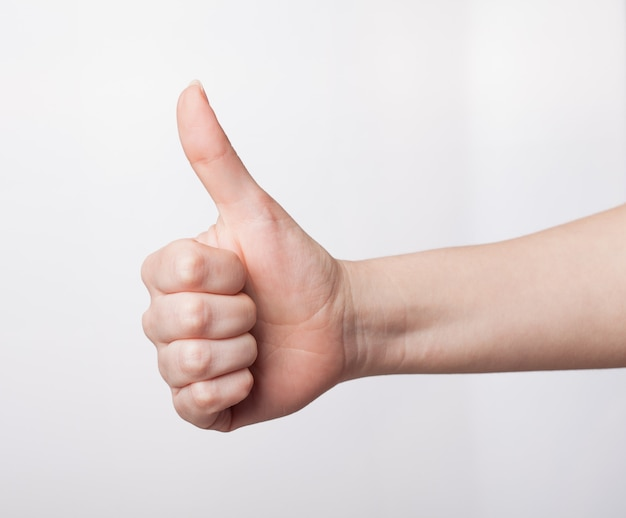親指を立てるジェスチャーを示す女性の手