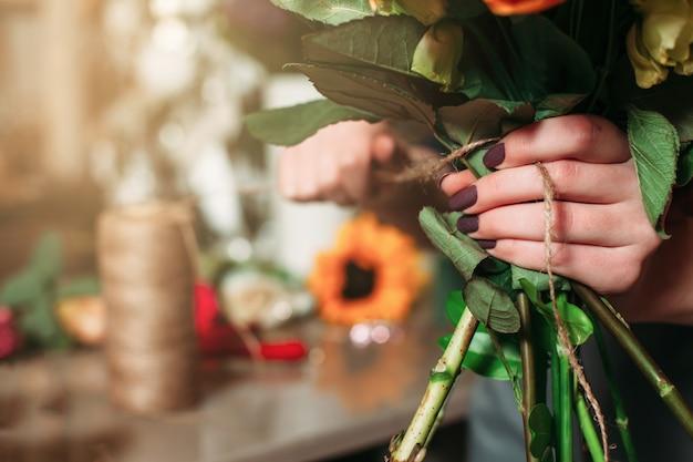 花の花束のクローズアップと女性の手