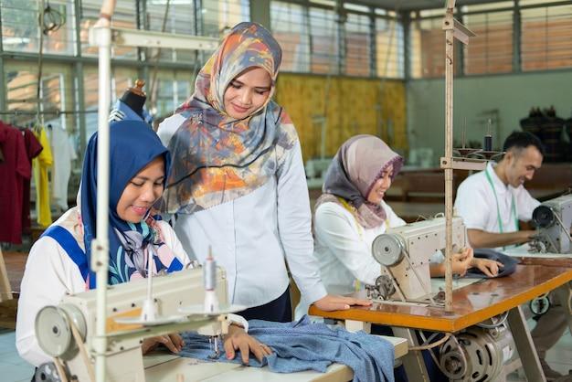 Надзиратель emale стоит в стороне и видит, как швея работает на швейной машине