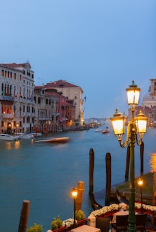 Embankment of grand canal at night, focus on lamp post venice, italy