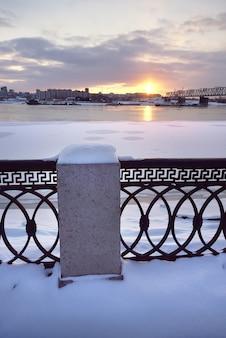 ノボシビルスクのオビ川の堤防。トランスシベリア鉄道橋の冬の日没