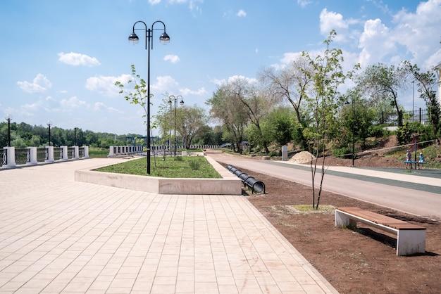 Urals summer의 제방 벤치와 자전거 주차장이있는 도시 제방의 음모