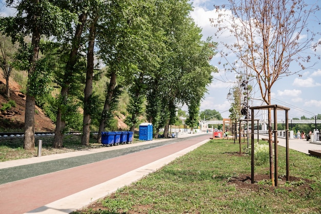 ウラル山脈の堤防植樹された木ごみ箱とコンポストトイレのある夏の都市の堤防