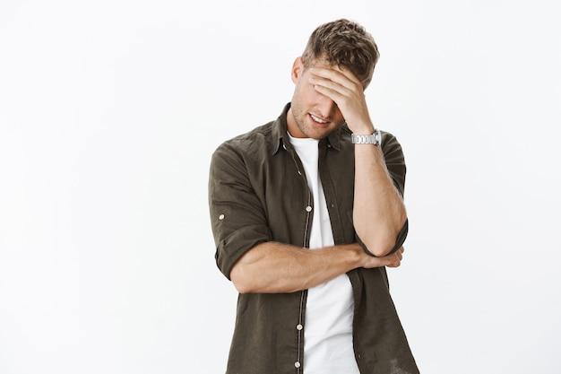 Смущенный и неловкий красивый бывший парень пытается спрятаться за руку, делая жест фейспалмом, чтобы женщина не узнала его, улыбаясь от стресса и беспокоясь, позируя на серой стене