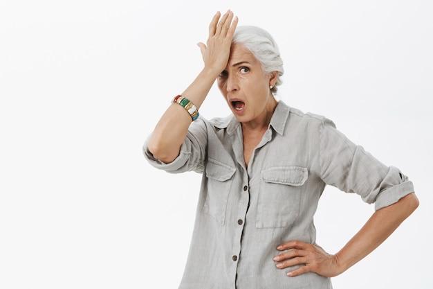 당황하고 충격을받은 고위 여성이 이마를 때리고 걱정을 찾고 있습니다.