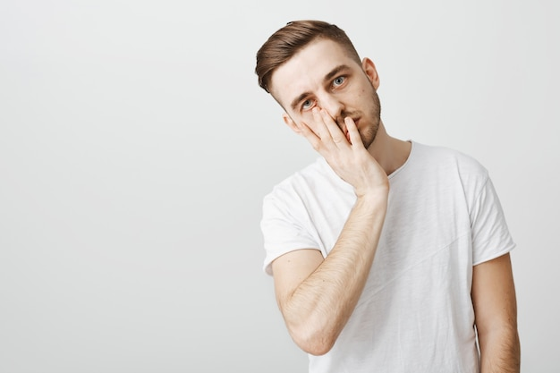 Embarrassed and annoyed guy looking exhausted and facepalm
