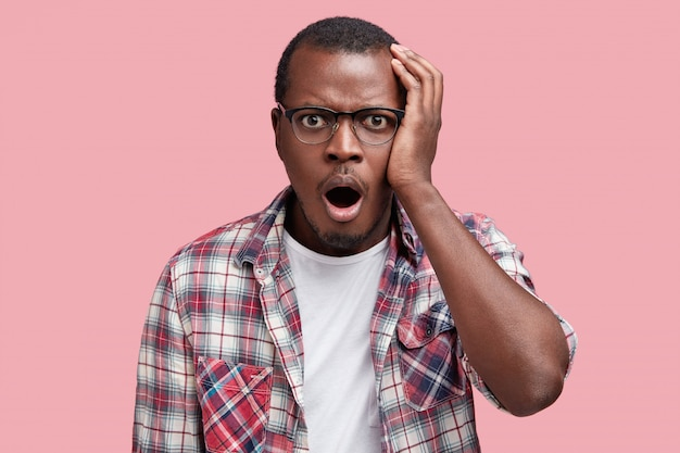 Embarrassed attractive african american male with shocked expression, dressed in checkred shirt and eyewear, expresses great amazement, isolated over pink