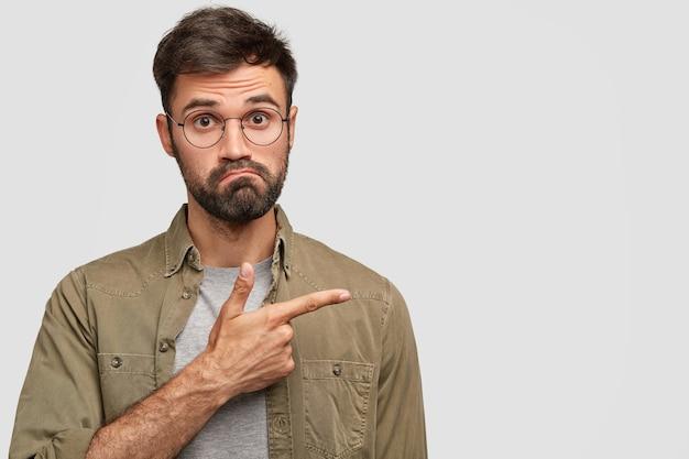 Смущенный бородатый мужчина поджимает губы и недоуменно смотрит, указывая в сторону указательным пальцем.
