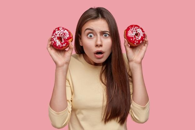 恥ずかしい美しい黒髪の女性はドーナツを保持し、表情を怖がらせ、困惑し、ピンクの背景の上に立っています