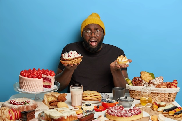 Embarrassed black fat bearded man holds two tasty cakes, cannot make choice what to eat, has tasty sweet breakfast, dressed in casual wear, isolated on blue wall.