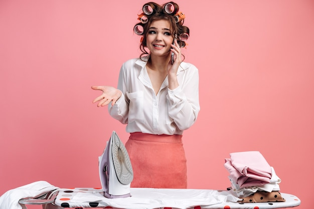 アイロン台で服にアイロンをかけている間、彼女の頭にカーラーが電話で話している恥ずかしいブルネット