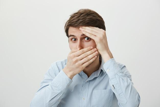 Смущенный симпатичный мужчина прикрывает глаза и заинтригованно заглядывает сквозь пальцы