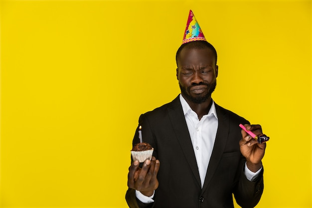 Embarrassed cute negro holding a birthday cake and whistle