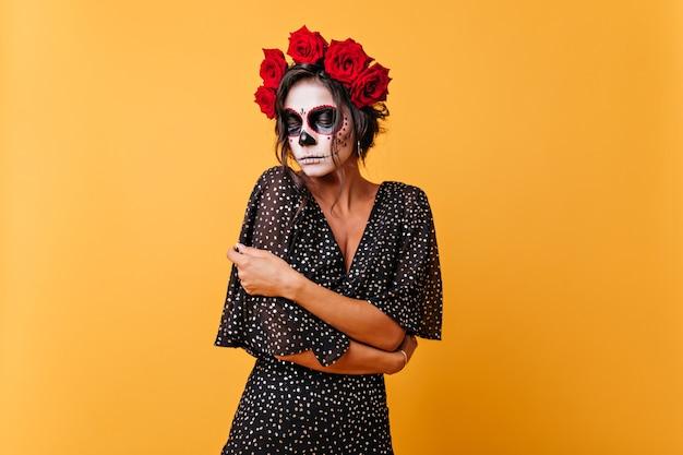 Ragazza dai capelli scuri imbarazzata con fiori sulla testa in posa nel tradizionale teschio di calavera. ritratto di modella messicana che guardava a terra