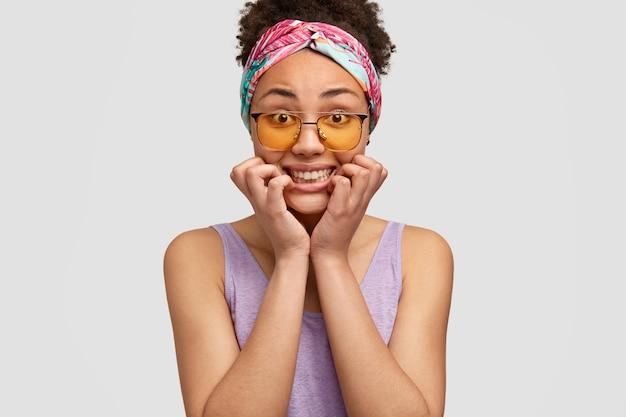 당황한 어두운 피부를 가진 젊은 여성이 꽉 치아 근처에 손을 유지합니다.