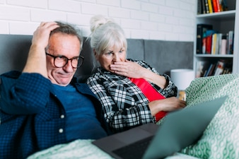 Embarrassed elderly couple in bed with laptop