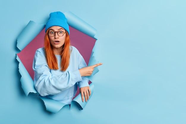 恥ずかしい感情的な赤い髪の女性が開いた口で立っているバグのある目は紙の穴を通してコピースペースを指しています