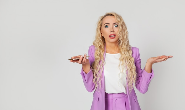 An embarrassed and excited blonde woman does not know what she did wrong, shrugs and shrugs her hands upset, holds a smartphone