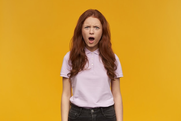 당황한 소녀, 긴 머리를 가진 불행한 빨간 머리 여자. 분홍색 티셔츠를 입고. 사람과 감정 개념. 그녀가 보는 것에 충격을 받았습니다. 오렌지 벽 위에 절연