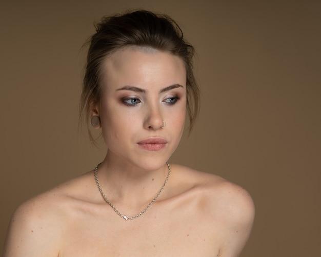 Смущенная девушка с гетерохромией, пирсингом в носу и затычкой в одном ухе и странной прической. с потрясающим профессиональным макияжем и серебряной цепочкой на шее. бежевый фон. студийный снимок