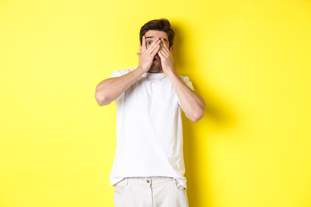 Embarrassed guy shut eyes but peeking through fingers at something awkward, standing over yellow background.